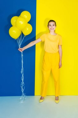 Female fashion model holding bunch of yellow balloons on blue and yellow background