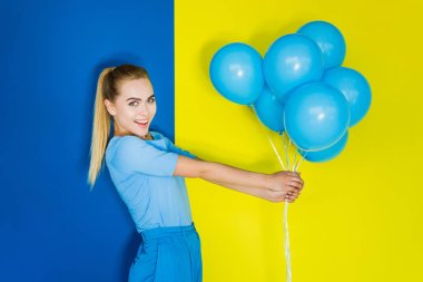 Attractive young girl holding bunch of blue balloons on blue and yellow background