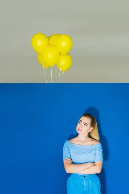 Sad blonde woman looking at balloons under the ceiling on blue background stock vector
