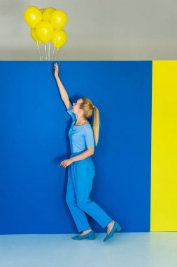 Beautiful blonde girl reaching out for yellow balloons on blue and yellow background