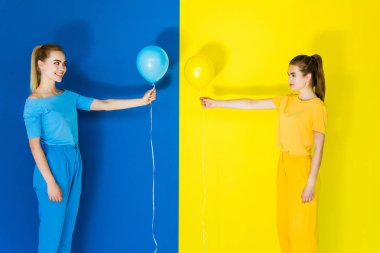 Beautiful blonde and brunette girls holding balloons in front of each other on blue and yellow background