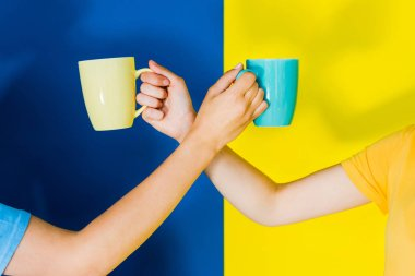 Cropped view of colorful cups in women hands on blue and yellow background
