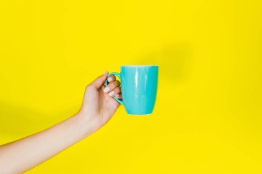 Cropped view of female hand with blue cup on yellow background