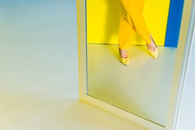 Cropped mirror view of woman wearing yellow shoes on blue and yellow background