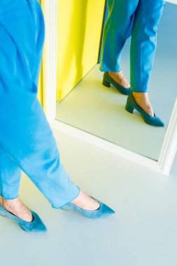 Cropped mirror view of woman in blue clothes and shoes on blue and yellow background