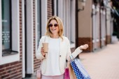 Fotografie smiling attractive woman walking with coffee to go and shopping bags on street
