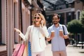 Fényképek beszélő smartphone and gazdaság bevásárló táskák, férfi és eldobható kávéscsészét utcán boldog nő