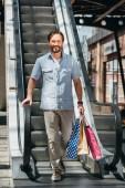 usmíval se pohledný muž v nákupní centrum s papírové tašky