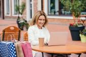 atraktivní žena pracující s notebookem u stolu v kavárně
