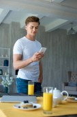 selective focus of man using smartphone and breakfast on table at home