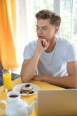 portrait of young pensive man sitting at table with breakfast and laptop at home
