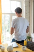back view of man standing at window with breakfast on table at home