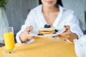 cropped shot of woman with pancakes served with blueberries on plate in hands at home