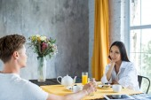 Fotografie side view of young multiracial couple having breakfast together at home