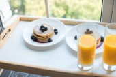 Fotografie close up view of glass of juice and pancakes for breakfast on wooden tray