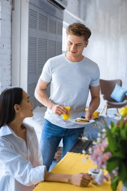 Caucasian man brought breakfast to asian girlfriend in white shirt at table at home stock vector