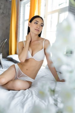 young beautiful asian woman in underwear resting on bed at home
