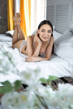 portrait of smiling asian woman in underwear lying on bed at home