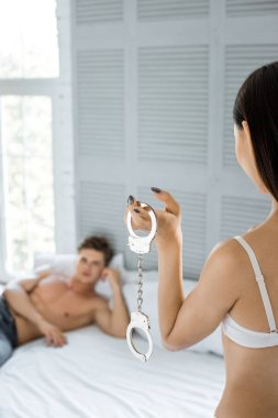 partial view of woman with cuffs and shirtless caucasian boyfriend lying on bed in bedroom