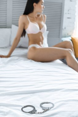 selective focus of cuffs and asian woman in underwear resting on bed at home