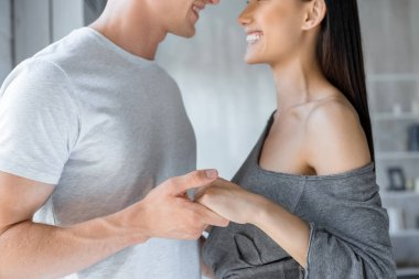 partial view of affectionate couple holding hands at home