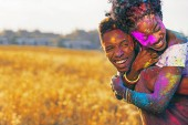 Fotografia laughing african american couple piggybacking at holi festival in wheat field