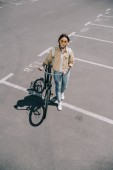 high angle view of stylish woman with bicycle at parking lot