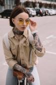 Fotografie atraktivní stylové Tetovaný žena stojící kolo na ulici