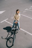 Fotografie high angle view of stylish woman with bicycle at parking lot