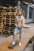 stylish tattooed woman standing with skateboard near wooden pallets