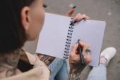 selektiven Fokus der tätowierte junge Frau in leer Lehrbuch schreiben
