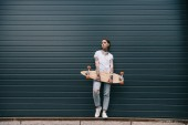 Fotografie distant view of young woman with tattoos holding skateboard against black wall