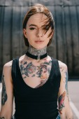 portrait of young attractive woman with tattoos looking at camera