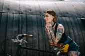 Fotografie smiling stylish tattooed girl standing with bicycle at street
