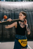Fotografie young stylish tattooed girl looking away and holding skateboard over shoulder