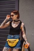 mladé stylové Tetovaný žena stojící s skateboard a nastavení sluneční brýle