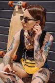 Tetovaný žena v sluchátka poslouchat hudbu s smartphone poblíž skateboard