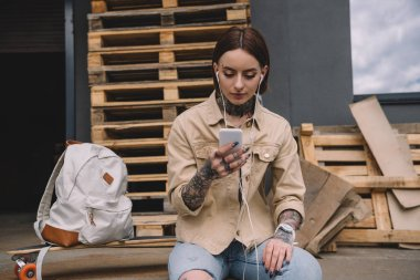 stylish tattooed woman in earphones listening music with smartphone near skateboard and backpack