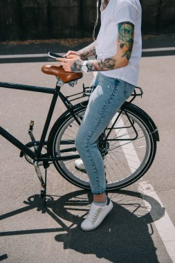 cropped image of tattooed woman in earphones listening music with smartphone while sitting on bicycle