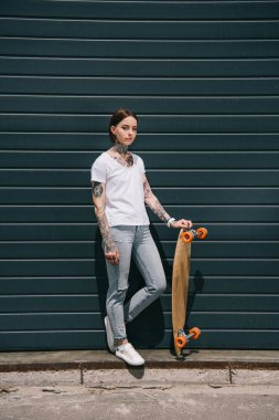 Young tattooed woman standing with skateboard against black wall stock vector