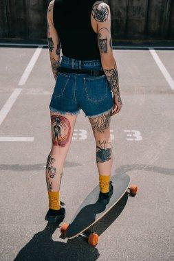 cropped image of stylish tattooed girl skateboarding at parking lot