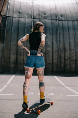 rear view of stylish tattooed girl with hands in pockets skateboarding at parking lot