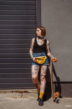 stylish tattooed girl with waist bag holding skateboard against wall