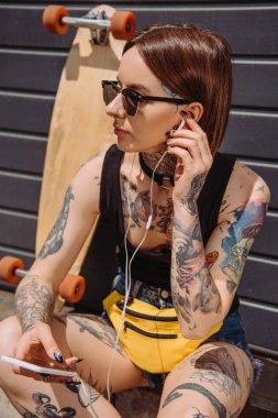 tattooed woman in earphones listening music with smartphone near skateboard