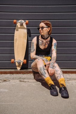 Stylish woman with tattoos sitting near skateboard at street stock vector