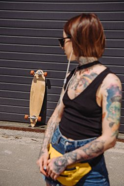 young tattooed woman listening music in earphones and looking at skateboard near wall