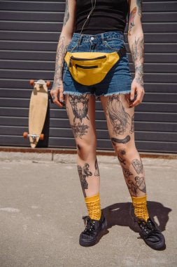 cropped image of stylish tattooed woman with waist bag