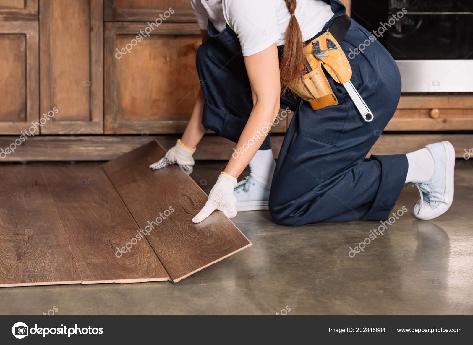Bijgesneden schot van repairwoman installeren laminaat keukenvloer