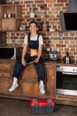 šťastné mladé repairwoman v jednotné sedí na kuchyňském stole a při pohledu na fotoaparát