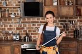 schöne lächelnde junge Reparaturfrau mit Maßband, die in der Küche steht und in die Kamera schaut